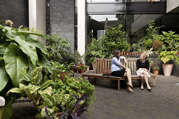 Two women sitting on a bench in the RCP garden