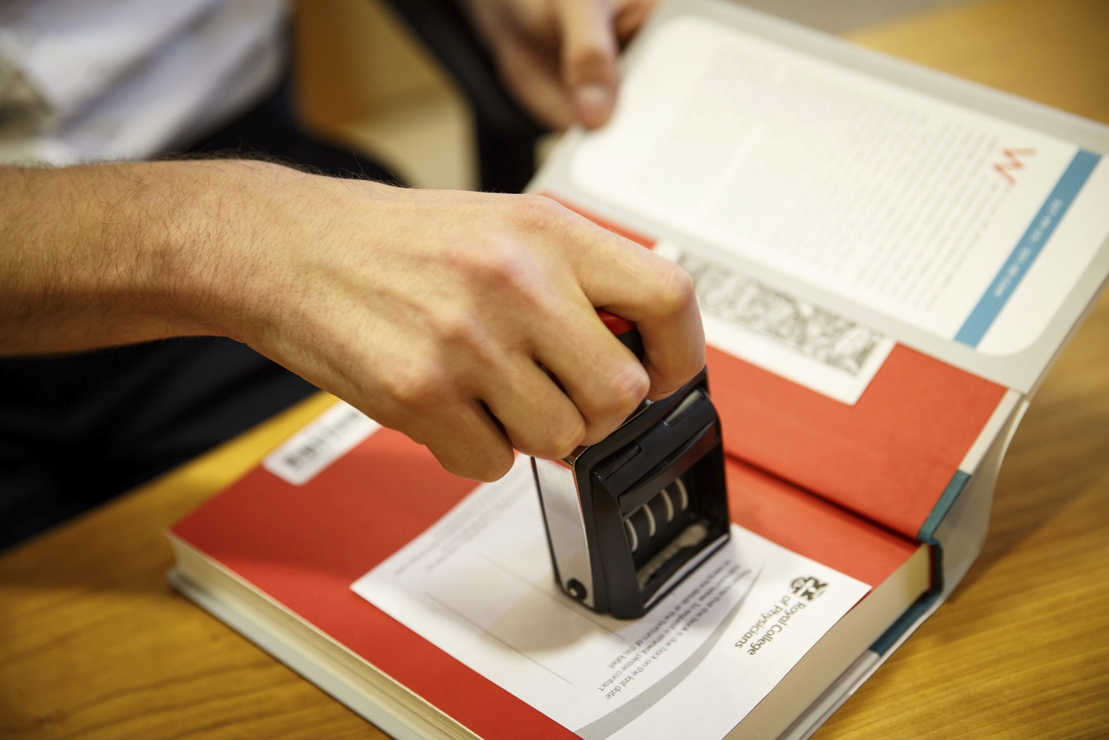 Librarian stamping a date in a book