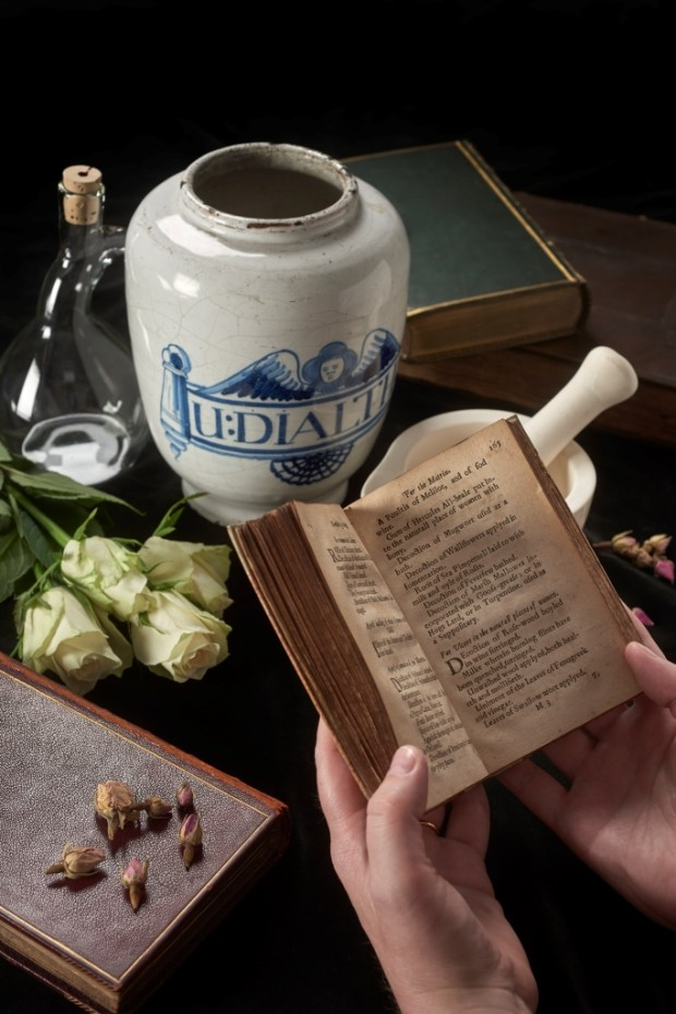 A copy of Leonard Sowerby's 1652 book 'The Ladies Dispensatory' is held open in front of an apothecary jar dating from around the 18th century