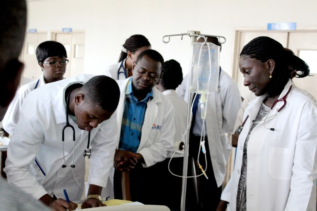 Group of doctors looking at man signing form